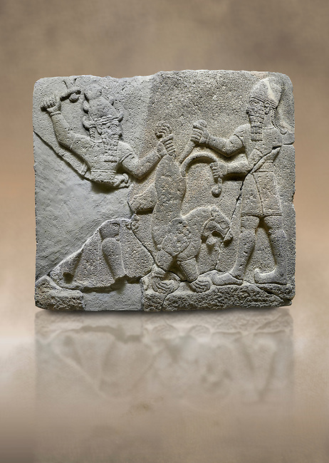 Hittite relief sculpted orthostat stone panel of Herald's Wall Basalt, Karkamıs, (Kargamıs), Carchemish (Karkemish), 900-700 B.C. Anatolian Civilisations Museum, Ankara, Turkey.<br /> <br /> On the right is a bearded human figure with a short skirt; with the dagger in his right hand, he is stabbing the lion standing on his front legs while holding the lion's tail with his left hand. On the left is a bearded god figure with a horned-headdress, who grasps the lion's hind leg while holding the ax over his head with his right hand. <br /> <br /> Against a brown art background.