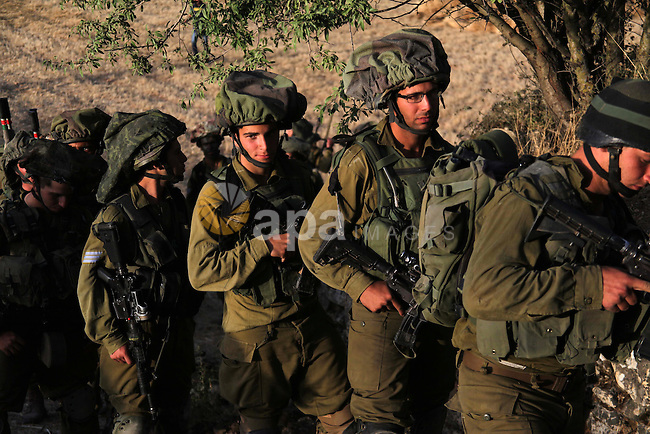Israeli troops take part in a search operation on the outskirts of the West Bank town of Hebron on June 16,2014 as security forces broadened the search for three teenagers believed kidnapped by Palestinian militants and imposed a tight closure of the town. Three Israeli teenagers, one of them also a US citizen, have been kidnapped in the occupied West Bank, presumably by Palestinians, the army said. Photo by Mamoun Wazwaz