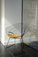 A Harry Bertoia chair is a stylish addition to the clean lines of a modern hallway decorated with white walls and Brazilian black slate flooring.