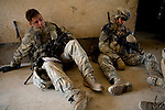 Sargeant Ryan Doolittle, left, and Specialist Ying Kit Tsui, right, of the 82nd Airborne's 1/508 Parachute Infantry Regiment, Alpha Company, Third Platoon nod off while taking a break from searching homes after staging a nighttime air assault into Sangin, Helmand province, the largest air assault in Afghanistan since the beginning of the war, on Thursday, April 5, 2007.