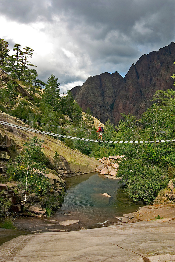 Corsica. Balagna. Hiker on the bridge at Spasimata, near Bonifatu, on the GR20 long distance walking track.  France..