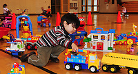 Pascal Lyon plays with toys, while other children ride tricycles, during the 9 AM to noon parent/child play time at Warner Park Community & Recreation Center on Friday
