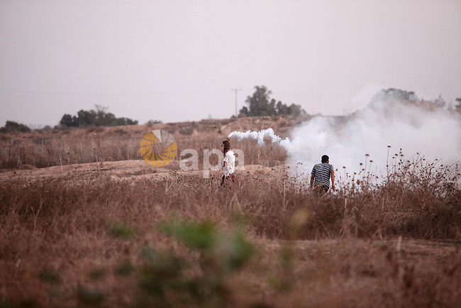 A Palestinian protester throws back a tear gas canister  towards Israeli troops during clashes near a border fence between Israel and the Gaza Strip on October 14, 2015 east of Bureij in central Gaza. The outbreak of violence between Palestinians and Israeli forces in recent weeks has worsened in October, raising fears of a third intifada, or uprising. Photo by Ashraf Amra
