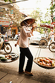 VIETNAM, Hanoi, a woman sells fruit on the street in front of Cafe Nang in the Old quarter