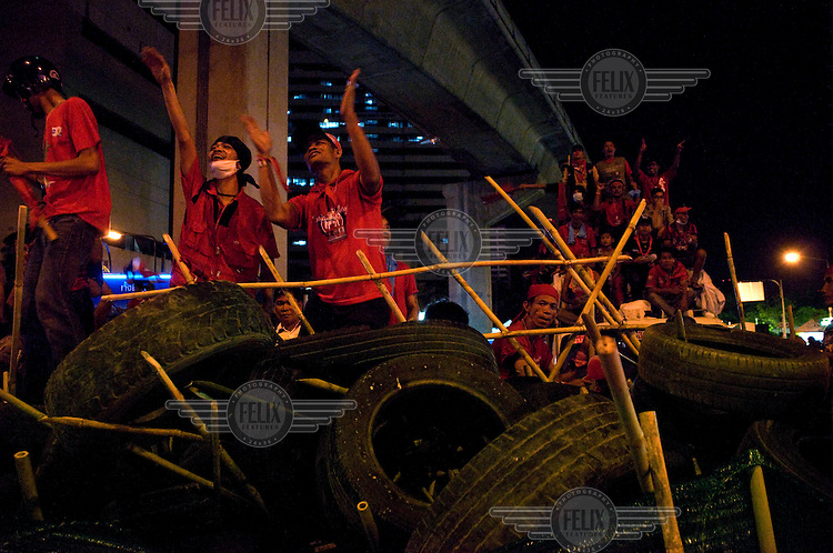 Red Shirt protesters sit on barricades at the intersection of Silom and Rama 4 road in Bangkok's busy financial district.