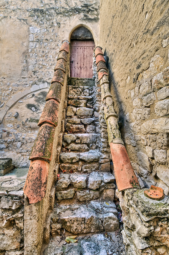 A narrow stairway made of stone with handrails of clay tiles, in the hilltop village of Ventabren.