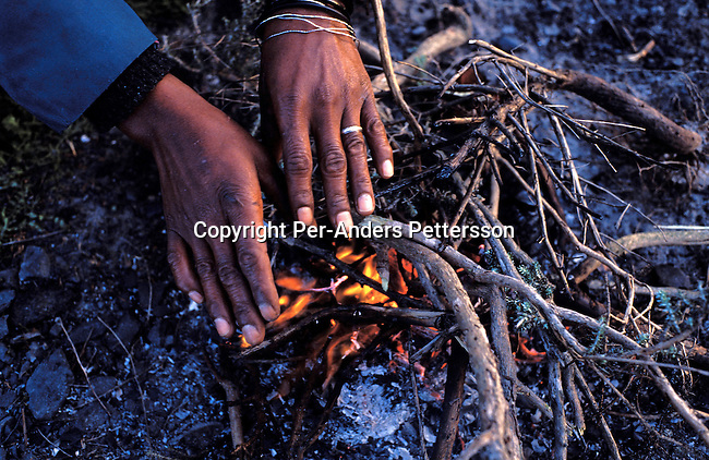 dienerg00033.Energy. A farm worker warming her hands over a fire at sunrise before a she's transported to a fruit farm in Stellenbosh about 70 kilometers from Cape Town on August 4, 2001 in Site B Khayelitsha, a township about 35 kilometers outside Cape Town, South Africa. Khayelitsha is one of the poorest and fastest growing townships in South Africa. People usually come from the rural areas in Eastern Cape province to find work as maids and laborers. Most people don't find work and the unemployment rate is very high, together with lot of violence and a growing HIV-Aids epidemic itÕs a harsh area to live in..©Per-Anders Pettersson/iAfrika Photos.