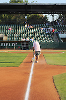 The grounds crew paints the third base line prior to the Pioneer League game between the Helena Brewers and the Ogden Raptors at Lindquist Field in Ogden Utah on July 20, 2013.  (Stephen Smith/Four Seam Images)