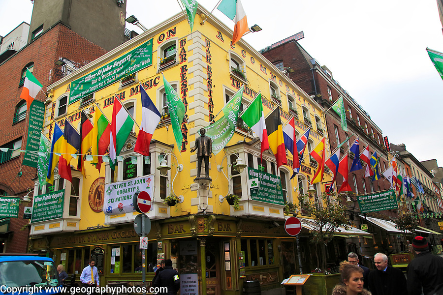 Flags outside colourful yellow Oliver St John Gogarty pub in Temple Bar area, Dublin city centre, Ireland, Republic of Ireland