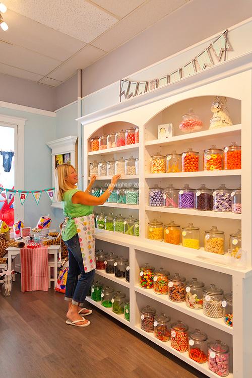 Proprietor Dana Hueberger re-stocking the candy shelves in her store, Sugar Sugar, in Salem, Oregon