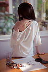 Sensual artistic portrait of a young woman Japanese Sumi-e painter with a bared shoulder revealing a sakura blossom body art painting on her back Image © http://MaximImages.com Image © MaximImages, License at https://www.maximimages.com