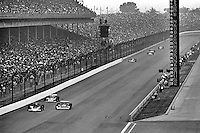 INDIANAPOLIS, IN- MAY 29: Al Unser leads a group of cars past the pit lane in his Parnelli VPJ6B 001/Cosworth TC during the Indianapolis 500 on May 29, 1977, at the Indianapolis Motor Speedway in Indianapolis, Indiana.
