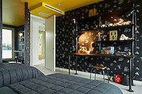 A bold, fun wallpaper with insect motifs and a bright yellow ceiling provides a dramatic backdrop to a teenager's bedroom. A scaffolding desk with sandblasted scaffolding wood, as a desk top material and for shelving, which was given a black paint finish. Industrial style clip on lights were added too.