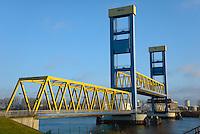 Kattwyk Bruecke: EUROPA, DEUTSCHLAND, HAMBURG, (EUROPE, GERMANY), 01.03.2013: Die Kattwyk Bruecke ueber der Suederelbe ist eine 290 Meter lange Hubbruecke mit zwei 70 m hohen Endportalen fuer den Eisenbahn- und Straßenverkehr. Sie verbindet Moorburg mit der Elbinsel Wilhelmsburg und wurde am 21. Maerz 1973 eingeweiht. Mit einer Hubhoehe von 46 m handelt es sich um die groesste Hubbruecke der Welt.<br /> Die Bruecke besteht aus zwei Trapezfachwerken ueber den Seitenoeffnungen und einem parallelgurtigen Fachwerkbalken ueber der Hauptoeffnung, der an 32 Stahlseilen aufgehaengt.<br /> Eine Besonderheit der Bruecke ist, dass die Eisenbahnschienen auf der Bruecke in der Mitte der Straßenfahrbahn verlaufen. Da sich Schienen- und Straßenverkehr die Kattwyk-Bruecke teilen, muss diese für die Durchfahrt eines Gueterzuges mittels Schrankenanlagen fuer den Straßenverkehr gesperrt werden.