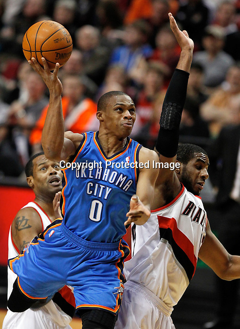 Oklahoma City Thunder point guard Russell Westbrook (0) shoots as Portland Trail Blazers power forward LaMarcus Aldridge (right) and center Marcus Camby (left) defend during first quarter of NBA basketball game in Portland, Oregon,  February 6, 2012.  REUTERS/Steve Dipaola (UNITED STATES)