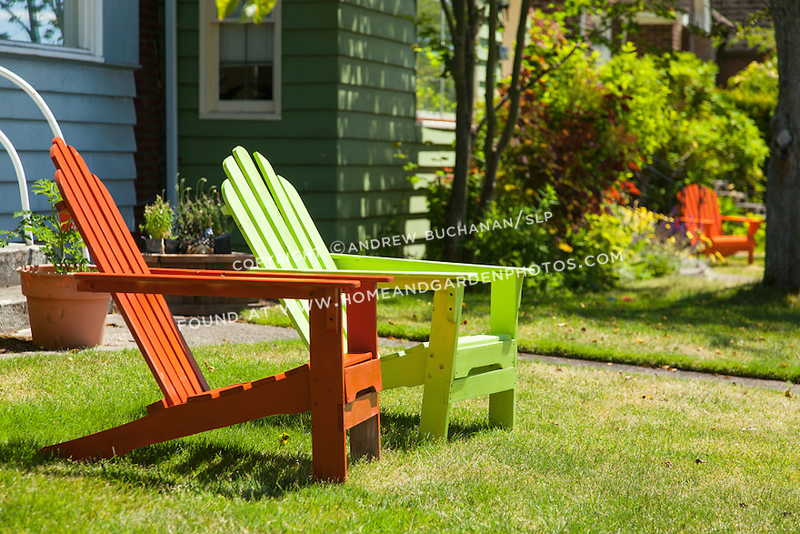 Colorful Adirondack chairs offer a welcome spot to sit in the sun in the backyard of a Seattle home.