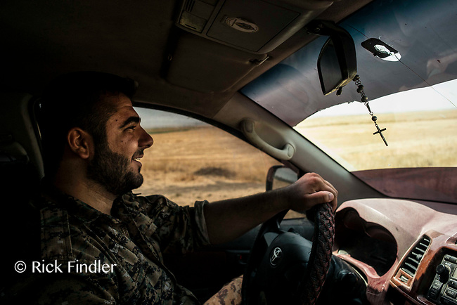 August 2017. Rojava, Syria.<br /> Joudi, a soldier of belonging to the MFS, drives his car toward the front lines of Raqqa. <br /> The MFS (Syriac Military Council) are a group of Assyrian Christians who fight alongside the Syrian Democratic Forces in the fight to topple ISIS.<br /> Photographer: Rick Findler