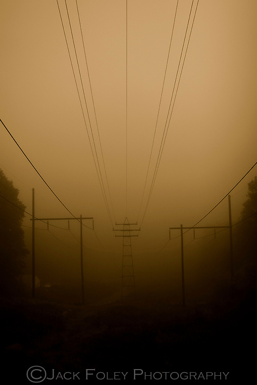 Power lines cutting through the landscape in the fog.