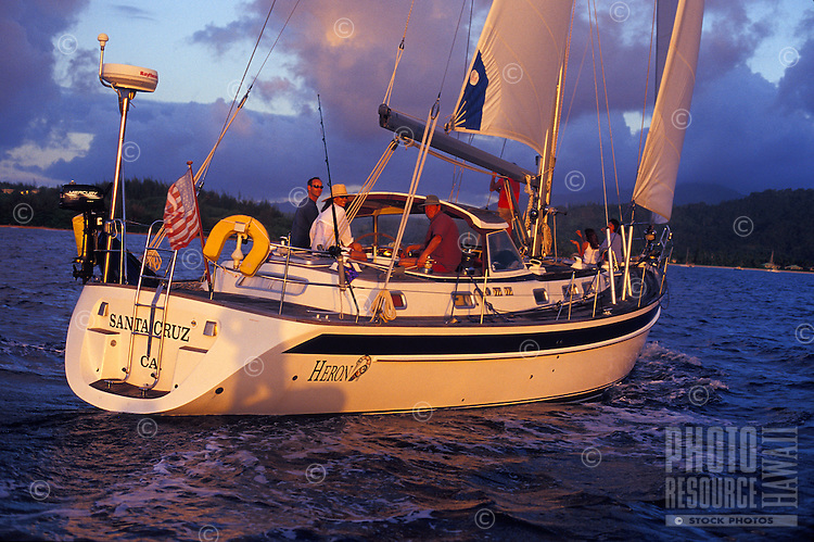 Family sailing a 48 foot yacht at sunset in Hanalei Bay, North Shore of Kauai