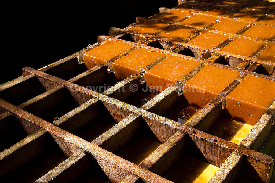 Rectangular panela blocks in a wooden mold during the processing of panela in a rural sugar cane mill (trapiche) in San Agustín, Colombia, 18 April 2004. Panela, a solid block of raw, unrefined sugar, is made by cooking and evaporation of the sugar cane juice into a golden, sticky syrup which is then poured into the wooden molds and allowed to solidify. Having the taste like a cross between molasses and brown sugar, panela is served as a hot or cold infusion (aguapanela). Due to the large amounts of proteins, vitamins and minerals and thus, panela is believed to have healing powers. Cheaper than sugar, it is consumed by the majority of Colombians and it is a major source of calories for children from families with low socioeconomic status. With more than 70,000 farms that cultivate sugarcane for mills, panela production is an important economic activity in the Colombian countryside, employing around 350,000 people and being the second largest source of jobs after agricultural coffee production.