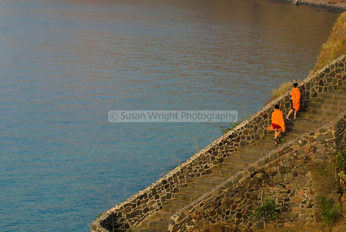 Two boys with orange towels walking up stone pathway, Salina, Eolie Islands, Sicily, Italy