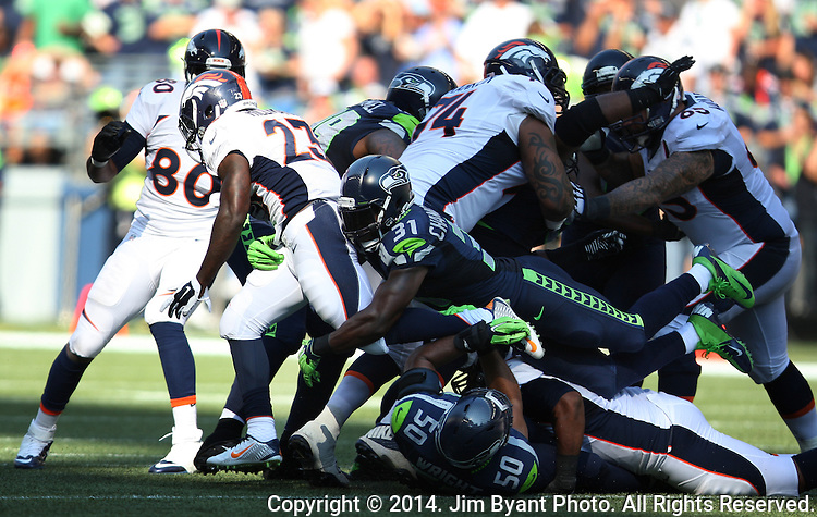 Denver Broncos running back Ronnie Hillman is brought down by Seattle Seahawks linebacker K.J. Wright (50) and strong safety Kam Chancellor (31) at CenturyLink Field in Seattle, Washington on September 21, 2014. The Seahawks won 26-20 in overtime.    ©2014. Jim Bryant Photo. All rights Reserved.