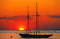 Silhouette of sailboat at sunset.
