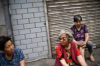 Women sit on a sidewalk outside closed businesses in Lanzhou, Gansu, China.