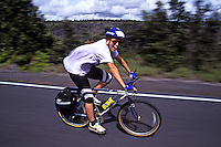 Woman biking through Hawaii Volcanoes national Park, Big Island