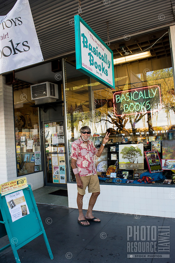 A local senior resident makes a peace sign in front of a shop along the waterfront at Kamehameha Avenue in downtown Hilo, Big Island of Hawai'i.
