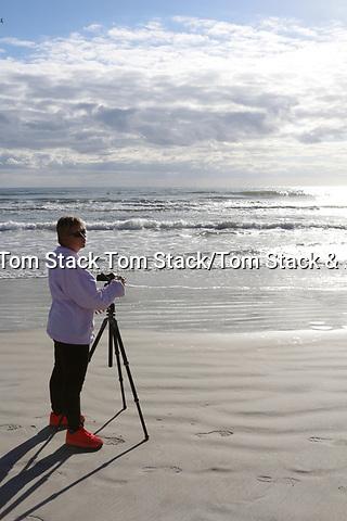 A woman videographer on the Atlantic ocean beach