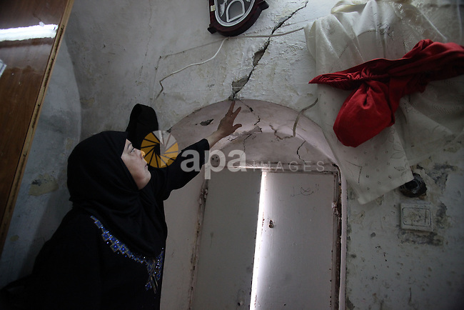A Palestinian woman gestures to the cracks on a wall at her home in the old town of Jerusalem, Nov. 23, 2013. Landslides began seven years ago due to the network of tunnels that Jerusalem's municipality is digging that endangers many homes in the area. Photo by Saeed Qaq