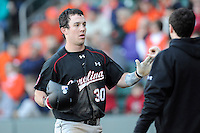 Designated hitter Elliott Caldwell (30) of the South Carolina Gamecocks is congratulated after scoring a run in the Reedy River Rivalry game against the Clemson Tigers on March 1, 2014, at Fluor Field at the West End in Greenville, South Carolina. South Carolina won, 10-2. (Tom Priddy/Four Seam Images)