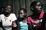 KINSHASA, DEMOCRATIC REPUBLIC OF CONGO - APRIL 29: Esther Yandakwa (c), age 9, smokes marijuana in a drug house on April 29, 2006 in Matonge district in central Kinshasa, Congo, DRC. Esther is homeless and works as a prostitute together with four friends. The girls live outside next to a polluted river. Esther has been on the streets for about three years, and has been rejected by her family. From time to time, she lives in a homeless shelter for but doesn't like the rules there. She usually smokes cigarettes, marijuana and drinks whiskey. She charges the clients as little as US$ 1. About 15,000 children are estimated to live on the streets of Kinshasa. Congo, DRC is in ruins after forty years of mismanagement by the corrupt dictator and former president Mobuto Sese Seko. He fled the country in 1997 and a civil war started. The country is planning to hold general elections by July 2006, the first democratic elections in forty years. (Photo by Per-Anders Pettersson)