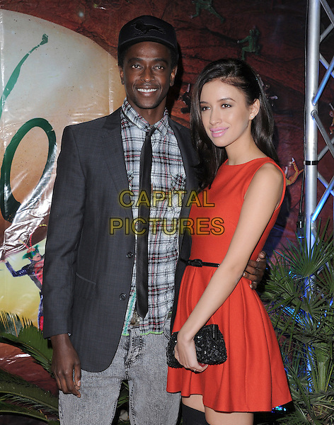 Christian Serratos and Edi Gathegi  .attending the Cirque du Soleil OVO Opening Night held at The Santa Monica Pier in Santa Monica, California, USA,.January 20th 2012..half length  sleeveless pink lipstick beauty make-up red dress black clutch bag belt cap hat grey gray shirt checked plaid tie jacket .CAP/RKE/DVS.©DVS/RockinExposures/Capital Pictures.