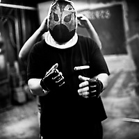 A fighter prepares for a fight, as another helps him strap up his helmet. 'Gentlemen's Fight Clubs' are held in private garages or homes. People who work as software engineers and programmers during the day meet there to fight. This way they are able to let out their tensions, frustrations and passions in somtimes overtly violent ways. The participants are known to use keyboards, dustbusters and rolled up women's magazines in their fights. Silicon Valley, California.