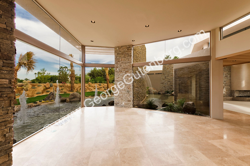 Large empty modern living room with travertine floors and view of water features