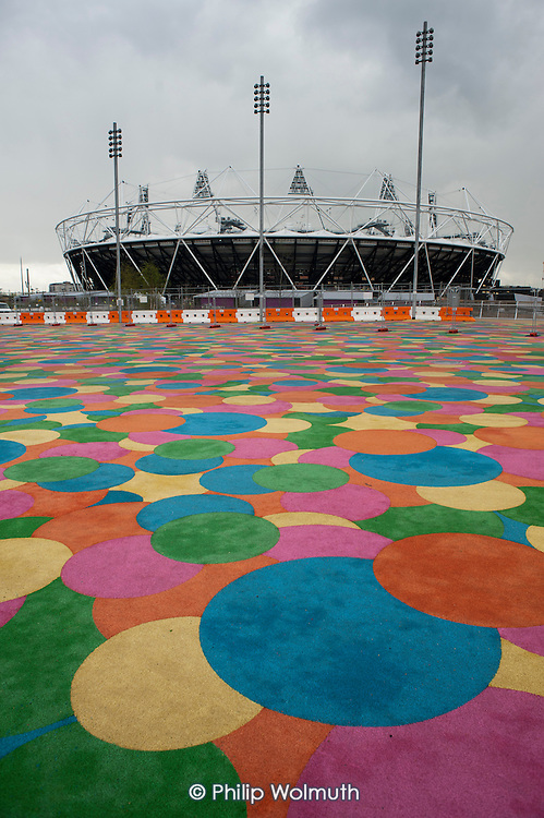 Multi-coloured parking area and the Olympic Stadium, London.