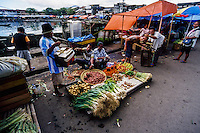 Indonesia, Sulawesi, Manado. Salesmen offering their goods on the market in Manado harbour.
