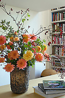 On a library table an colourful composition of pompom dahlias, roses and rosehips has been arranged in a ceramic vase with a rough bark-like glaze