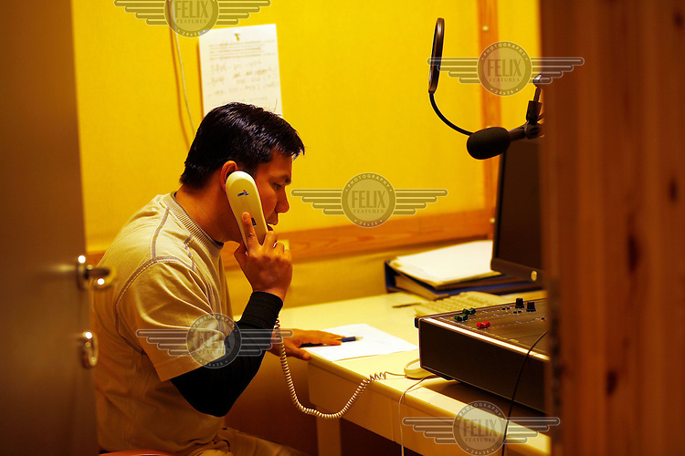 Journalist Htet Aung Kyan talks on the phone. Democratic Voice of Burma is radio and TV station run by exiled Burmese. Opposing the government, the DVB has been transmitting, from the Norwegian capitol Oslo, into Burma since 1992.