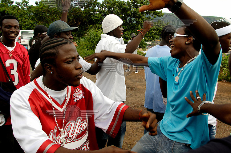 Members of the group 'X-taci' and friends dance during a break in the recording of their music video.  Music videos are becoming increasingly important as a meas of promotion, yet some of the most outspoken bands have suffered airplay bans imposed on their songs by government owned Sierra Leonean Broadcasting service (SLBS).  A new musical genre combining rap, Hip-Hop rhythms and protest lyrics has emerged in Sierra Leone following the brutal ten year long civil war.  The music is widely regarded as conveying the 'voice of the people' and representing the conditions of the country's younger generation during its post conflict period...