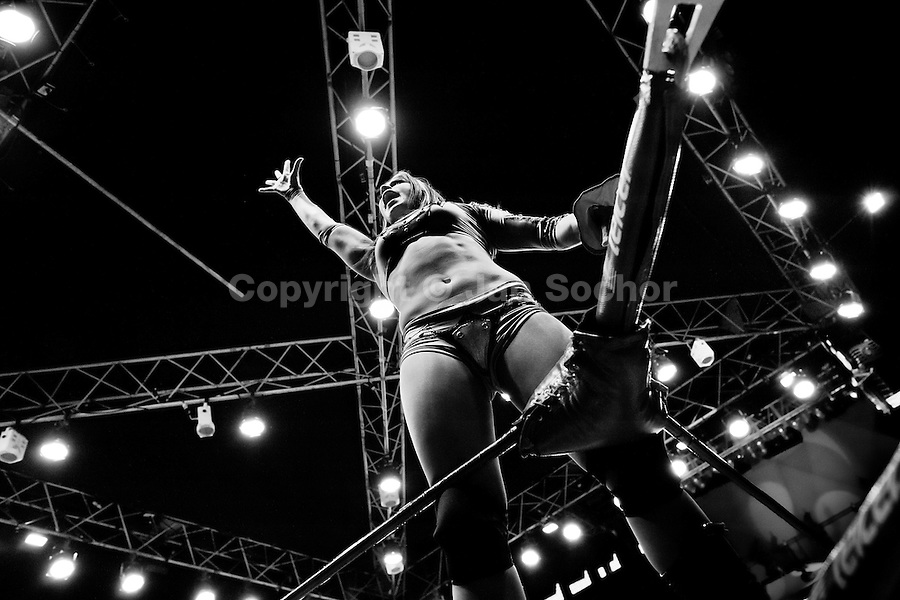 """A female Lucha libre wrestler Dark Angel stands on the ropes of the ring to excite the crowd during a fight at Arena Mexico in Mexico City, Mexico, 26 April 2011. Lucha libre, literally """"free fight"""" in Spanish, is a unique Mexican sporting event and cultural phenomenon. Based on aerial acrobatics, rapid holds and the use of mysterious masks, Lucha libre features the wrestlers as fictional characters (Good vs. Evil). Women wrestlers, known as luchadoras, often wear bright shiny leotards, black pantyhose or other provocative costumes. Given the popularity of Lucha libre in Mexico, many wrestlers have reached the cult status, showing up in movies or TV shows. However, almost all female fighters are amateur part-time wrestlers or housewives. Passing through the dirty remote areas in the peripheries, listening to the obscene screams from the mainly male audience, these no-name luchadoras fight straight on the street and charge about 10 US dollars for a show. Still, most of the young luchadoras train hard and wrestle virtually anywhere dreaming to escape from the poverty and to become a star worshipped by the modern Mexican society."""