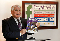 NWA Democrat-Gazette/DAVID GOTTSCHALK Steve Clark, president and chief executive officer of the Fayetteville Chamber of Commerce, displays Friday, January 11, 2019, the new workforce textbook A Calling at a press conference at the chamber office in Fayetteville. The book has 28 local employers describing the career pathways in their organization. The textbook will be distributed to every middle and high school student attending Fayetteville Public Schools. The textbook will be used by the teachers during their CTE classes.