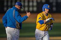 Delaware Blue Hens head coach Jim Sherman (left) slaps hands with Zach Lopes (19) as he rounds the bases after hitting a solo home run in the top of the 9th inning against the Georgetown Hoyas at Wake Forest Baseball Park on February 13, 2015 in Winston-Salem, North Carolina.  The Blue Hens defeated the Hoyas 3-0.  (Brian Westerholt/Four Seam Images)