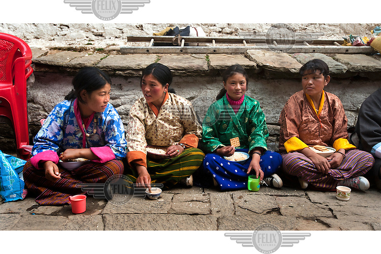 A group of female pilgrims eat at the Tango Dzong Monastery.