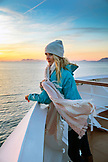 CANADA, Vancouver, British Columbia, female passenger enjoying the views at sunset of Discovery Passage in the Inside Passage, Holland America Cruise Ship the Oosterdam