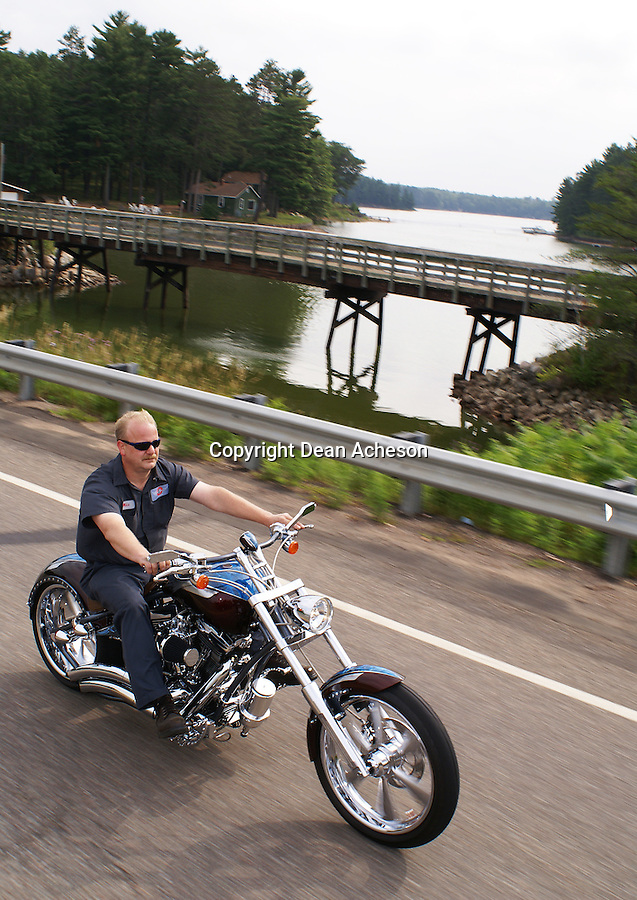 A motorcyclist rides past a lake in Lincoln County, WI, just before the motorcycle rally called Ride to Tomahawk, held each fall in Tomahawk, WI and surrounding communities.