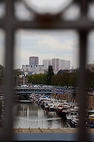 The view of the port de l'Arsenal, at the mouth of the canal de Saint Martin, with its boats and its typical bridge, on the background of the skyscrapers dominating the panorama on the other side of the Seine river, as seen through the grille which closes this side of place de la Bastille in Paris. Digitally Improved Photo.