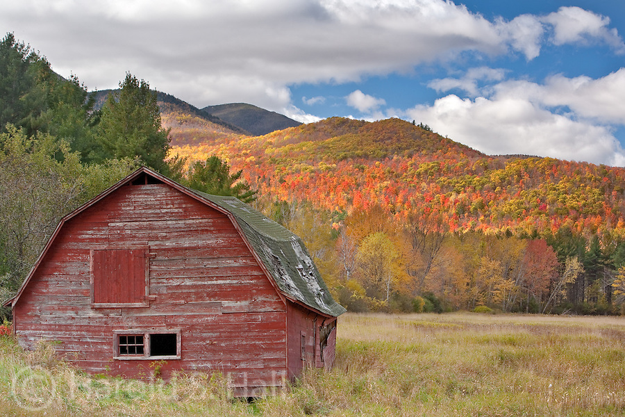 An old weathered barn makes it through another fall season with vivid fall colors on the near-by mountain.